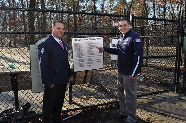 Image of two men beside sign on a fence