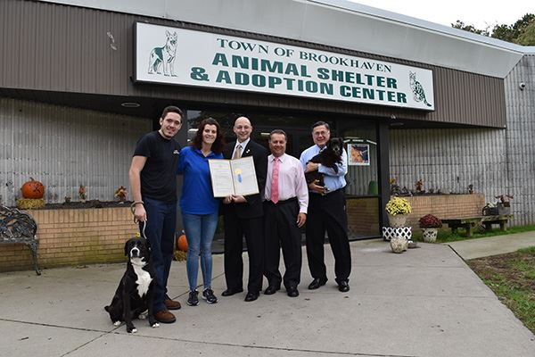 Image of five people outside animal shelter with two dogs