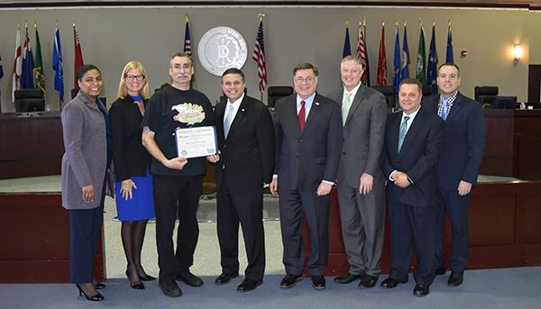 Man holding award certificate with councilmen