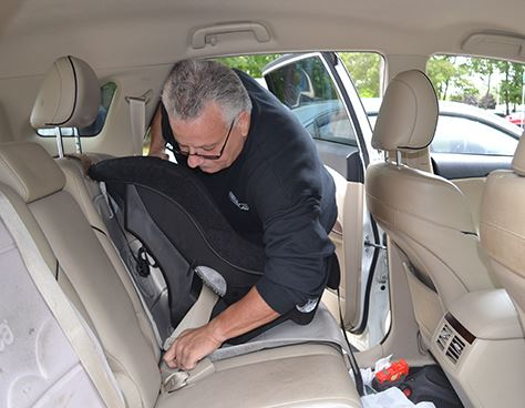 Man Buckling Car Seat Into Car