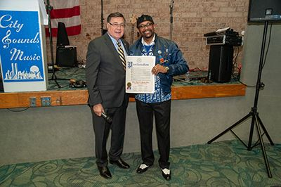 Supervisor Romaine presenting a proclamation to Jerome Smith