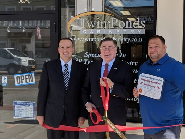 Three men at ribbon cutting outside shop