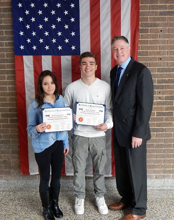 Two high school students holding awards beside councilman