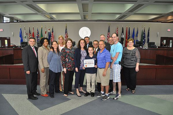 Middle school student holding certificate surrounded by adults