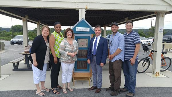 Six people at Little Free Library