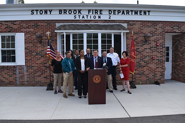 Man at podium with small group of people in front of fire department