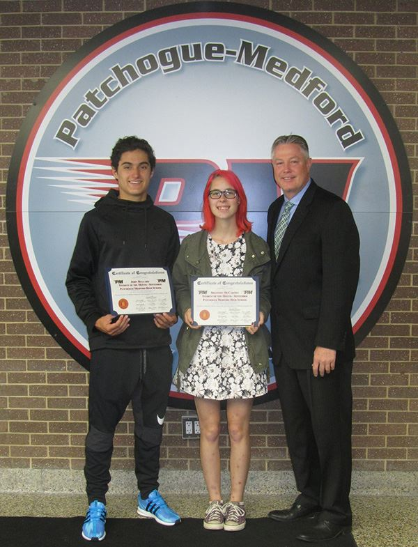 Two students holding certificates beside councilman
