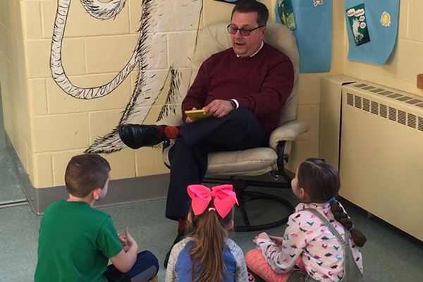 Councilman reading to students sitting on floor