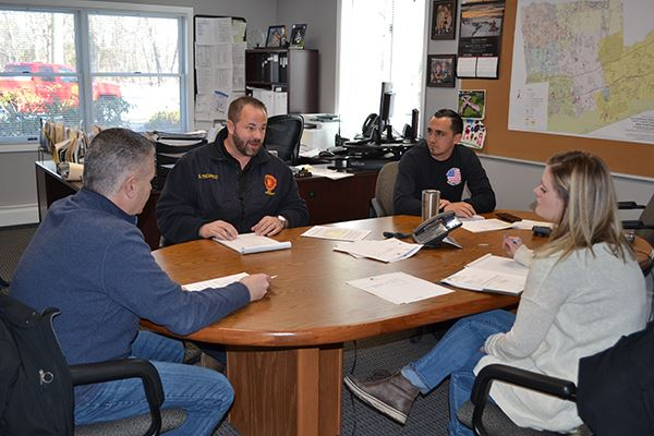 Town Highway Department Employees Sitting Around Desk