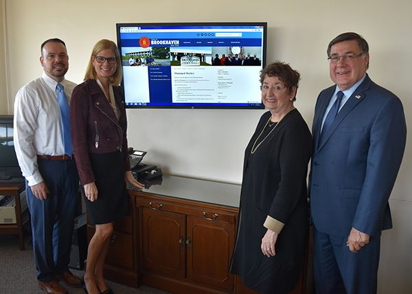 Town officials standing in front of computer screen