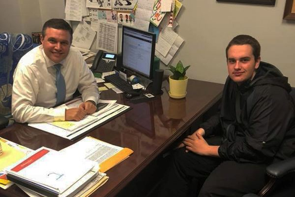 Student sits at Councilman's office smiling into camera