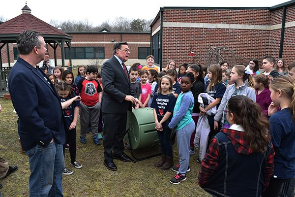 Mayor talking to children standing around compost bin