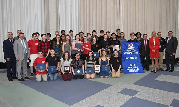 Robotics team stands with awards and councilmembers