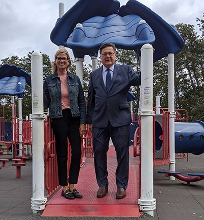 Councilwoman Bonner and Supervisor Romaine standing on playground equipment