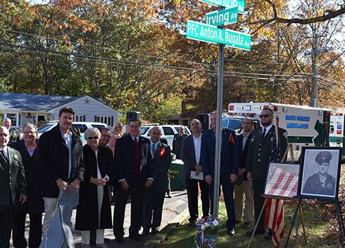 Elected Officials and Community Members Standing in Front of Street Sign