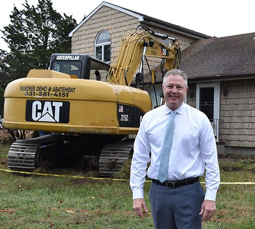 Councilman Foley standing in front of house