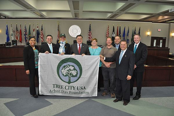 Supervisors and councilmen holding tree city USA flag