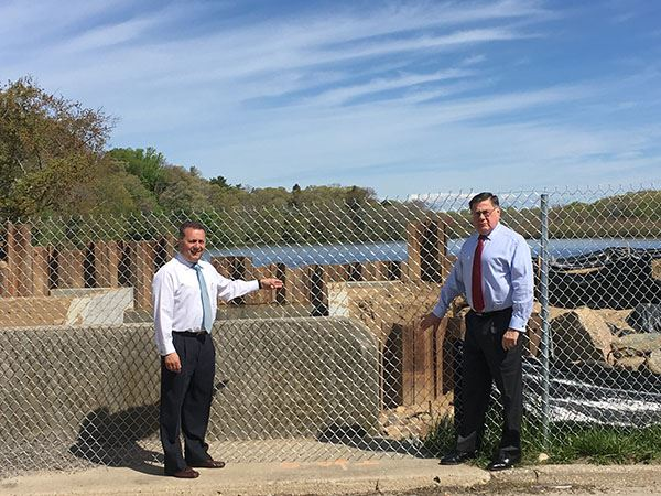 Supervisor and councilman at fence beside spillway