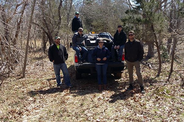 Group beside truck in woods