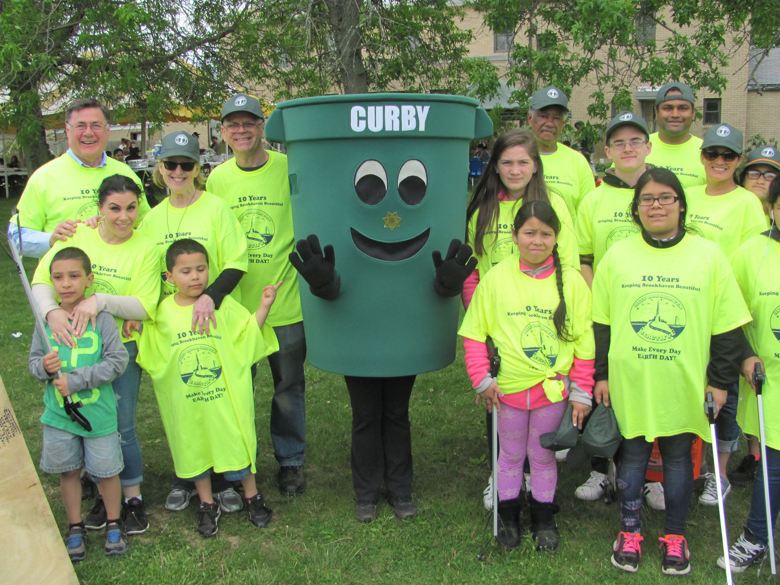 Group of adults and childern in yellow with recycling bin mascot