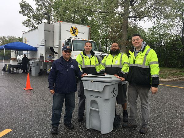 Four men at recycling bin outside