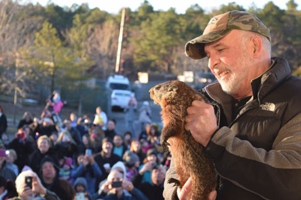 Man smiling holding groundhog