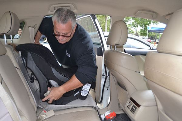 Man installing child seat in car