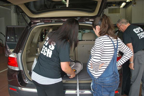 Two people help pregnant woman install child car seat