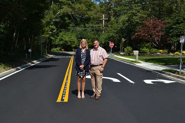 Man and woman standing on freshly paved road