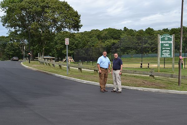 Two men standing on road in front of field