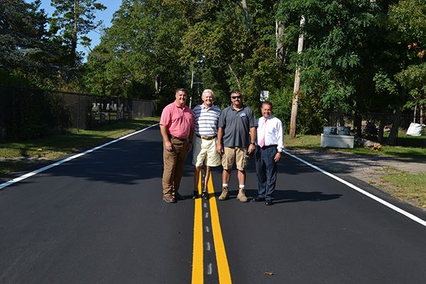 Four people standing on a freshly paved road