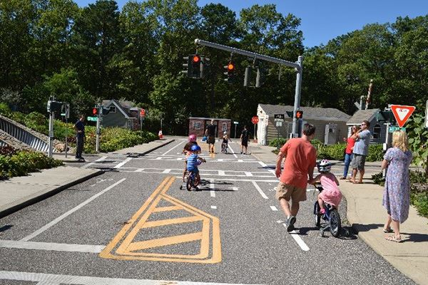 Children on bikes with parents in mock bicycle safety town