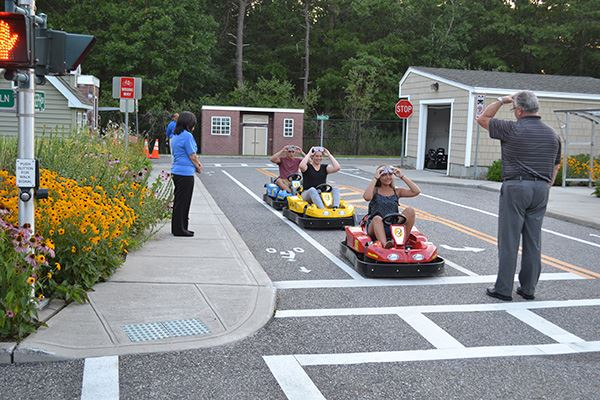 Teens in small toy cars in safety town