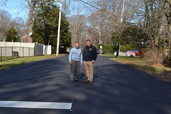 Two men standing in the middle of a neighborhood road
