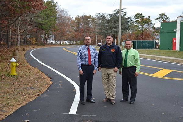 Three men standing on roadway