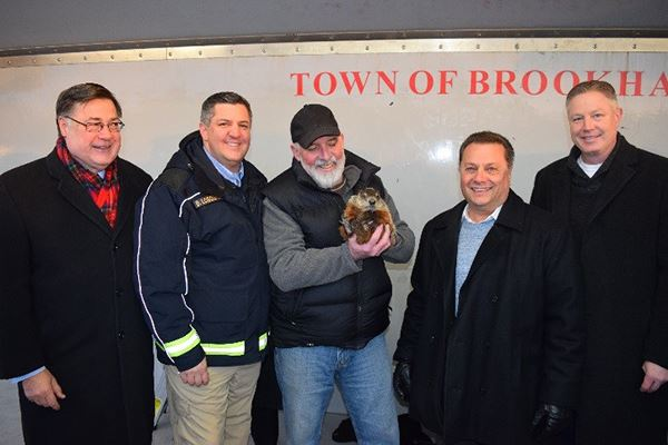 One man holds groundhog standing with three others