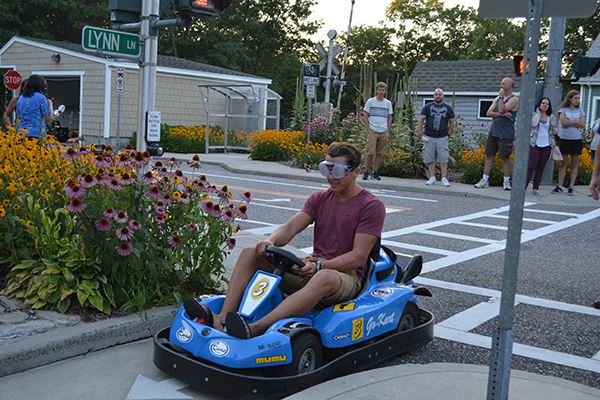 Teen drives electric toy car with beer goggles on