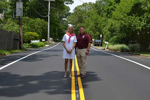 Woman and man standing together on paved road