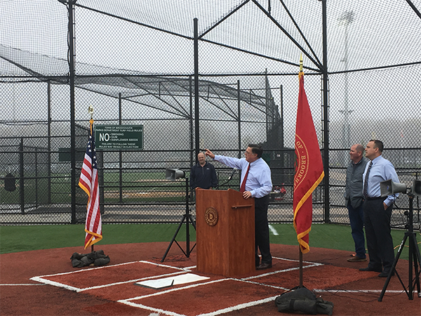 Supervisor Romaine at podium set up on baseball home plate