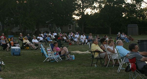 Crowd sitting in lawn chairs at dusk