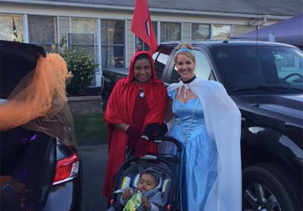 Two adults with baby in stroller in Halloween costume