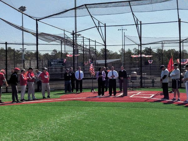 Business people at home plate of softball field