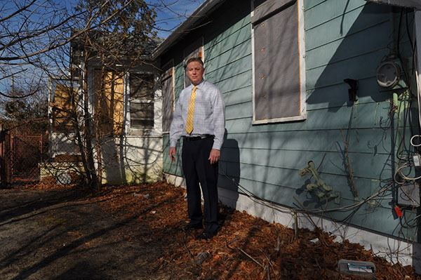 Man stands beside home to be demolished