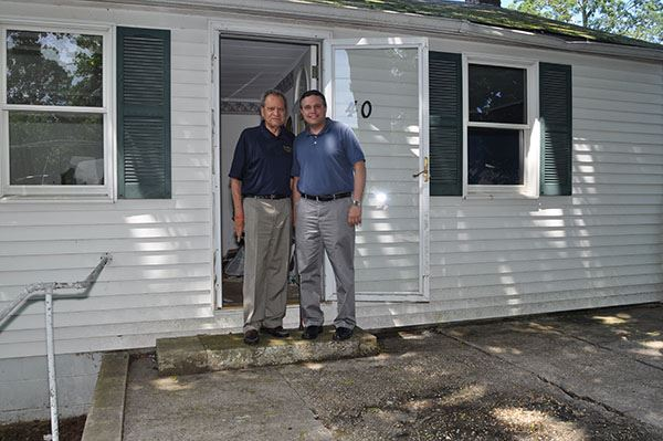 Two men stand on porch of home to be demolished