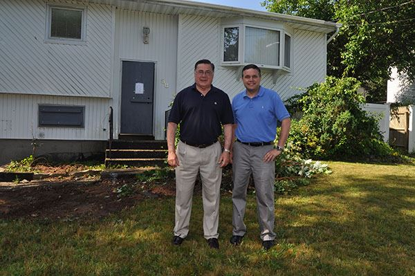 Two men stand outside white home to be demolished