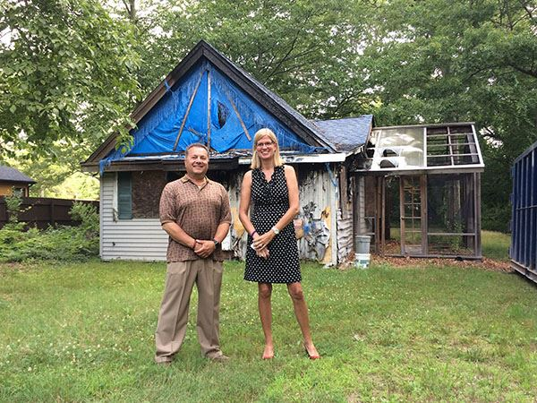 man and woman stand outside delapidated home