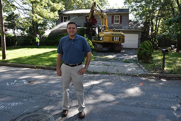 Man stands outside a home being demolished
