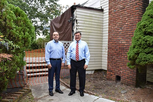 Two men stand on sidewalk of home to be demolished