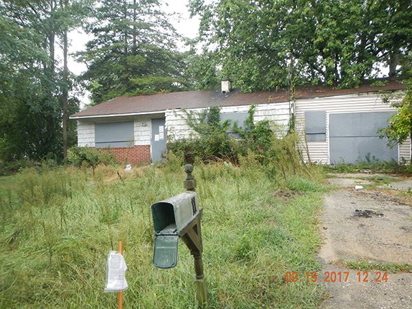Vacant home with overgrown yard
