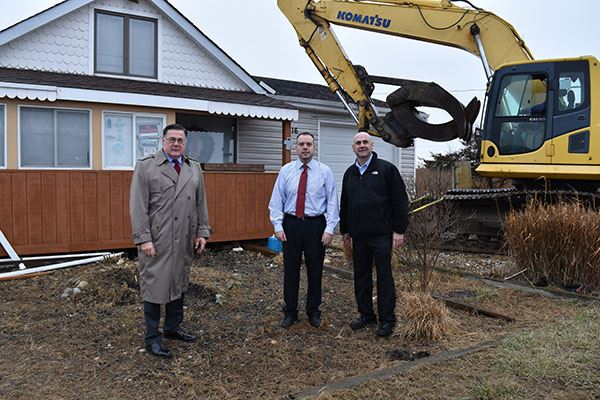 Three men standing outside house to be demolished
